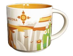 "14 ounce ""You Are Here"" 2013 Starbucks Collector coffee mug. Artwork features the Starbucks logo, cacti, and desert scenery printed against a pearl white background. Golden brown interior. Includes th"
