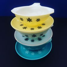 A stack of JAJ Pyrex Gaiety snowflake gravy boats in yellow, white and turquoise