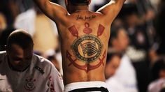 Torcedor do Corinthians mostra tatuagem do time, no estádio do Pacaembu