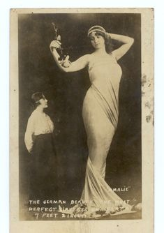 Full view of a tall woman holding a rose in a tightly wrapped dress. Another smaller woman looking up. Printed: Amalie / Ther German Beauty. The Most / Perfect Giantess on Earth / 7 feet 2 inches