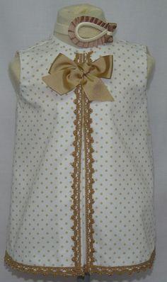 Vestido para bebe niña en piqué blanco con lunares camel, adornado con punta de bolillos camel y lazo a juego.