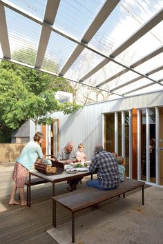 The family shares an alfresco lunch with Ikimau Ikimau, a friendly neighbor who helped build the house. The aluminum weatherboard cladding was custom-designed by O'Sullivan.