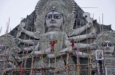 Workers on a bamboo scaffold give finishing touches to a huge idol of Hindu goddess Durga at a worship venue in Kolkata.