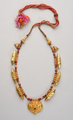 """Gold necklace incorporating elements similar to those often found in silver amulet necklaces (this, so to speak, is a """"luxury version""""). India; 2nd half 20th c. H of pendant at bottom = 4 cm. Gold (filled with e.g. pitch or lac), rubies, silk cord. A refined piece shown in Truus Daalder, *Ethnic Jewellery and Adornment*, p. 331."""