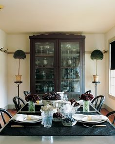"The unique proportions of the dining room allow for this oversize table, a great place for spreading out work after guests have left. Complementing the galvanized-steel tabletop are black-painted grange chairs and horsehair table mats in lieu of a conventional cloth. ""Black"" foods, including blueberries, black raspberries, grapes, and cherries, are set out on black-patterned English china. Bundles of black scabiosas complete the table setting. The large cupboard was unremarkable when Martha…"