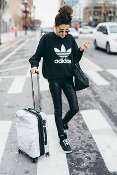 3 Winter Travel Style Staples | Hello Fashion. Black graphic sweatshirt+black and white striped tee+black faux leather pants+black sorel boots+black handbag+sunglasses. Fall Travel Outfit 2016