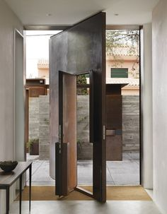 Studio Sitges by Tom Kundig Large panels of steel arch from the ground over the entrance, curving to create part of the building's roof.