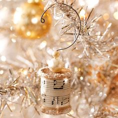Beautiful little ornament, a recycled thread spool with glitter at top & bottom, a strip of sheet music round the center, pearl & tiny gold beads on top & wire strung from bottom, up to curvy, fancy coat hanger-style hook at top for hanging.   ~  I love these! I so want to make some, I have lots of music sheets, & these other supplies. Can't wait to get started!