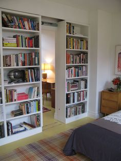 Bookshelf walls in a guest bedroom slide to reveal a small study.                                                                                                                                                                                 More