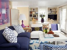 The designers added a pop of color in the accessories — like the purple lamp and throw pillows that match the curtains.