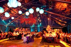 Teal and white lanterns float alongside light-painted floral arrangements to help create this beautiful color-saturated event