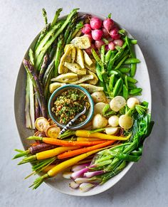 Instead of a classic raw crudites platter, try lightly poaching seasonal vegetables like snap peas, carrots, and asparagus. Serve the tender veggies with a lemony walnut relish. #fourthofjuly #fourthofjulypicnic #picnicrecipes #fourthofjulyfoods #bhg