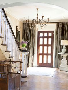 Love the curtains that can be drawn over the front door and side windows for privacy at night.  Such an elegant touch!  Via Traditional Home