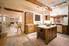 This kitchen showcases some great storage ideas, including the wine rack underneath the counter top. With an Aga, this kitchen would be very well suited to a cottage or period property. The classic stone tiled floor and multi-coloured tiles accentuate the dark wood of the cabinets perfectly.