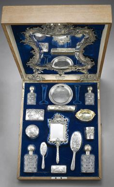 A silver dressing set, Fabergé and others, late 19th century. comprising: a dressing mirror with elaborate rocaille frame, a small round dish, circa 1900; two perfume bottles, a silver and glass box, a brush, an hand-mirror, and a circular box; together with an oval bowl, Kurliukov, Moscow, circa 1890, and a beaker, Paris, maker's mark PQ in lozenge, circa 1890; all contained in a velvet-lined fitted case, height of mirror: 60 cm. (23 ½ in.) (18)