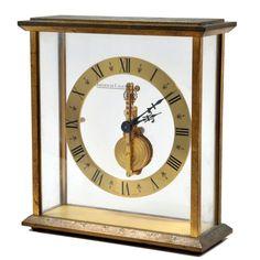 Relógio de mesa ` Jaeger Le Coultre` em bronze dourado e cristal, mostrador em algarismos romanos, funcionando. Meds: 17,0 cm x 15,5 cm x 6,0 cm