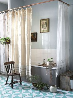 B L O O D A N D C H A M P A G N E . C O M: metal ring and white/creme shower curtains, icy grey blue walls, lively green plants, botanical print on the wall