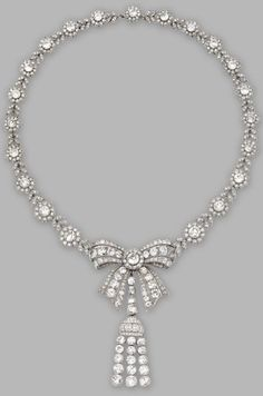 A Belle Epoque Platinum and Diamond Necklace, Cartier, Circa 1915. Designed as a bow in the centre supporting a detachable tassel, completed by a foliate motif necklace, set throughout with single-cut and old mine diamonds weighing a total of approximately 44.32 carats, length 16 inches, signed Cartier, numbered. #Cartier #BelleÉpoque #necklace