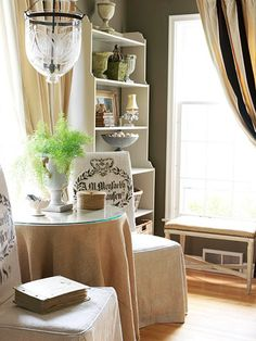 To make the style their own, the homeowners customized many of their accents with fabric. Natural fabrics such as burlap, hemp, velvet, and linen -- a Belgian specialty -- are used throughout the home. Antique hemp grain sacks printed with the owner's name and crest were repurposed as slipcovers for the Parsons chairs. The window treatments were also custom-made. The homeowners started with premade black, camel, and ivory striped velvet drapes, backed them in burlap fabric, and added a…