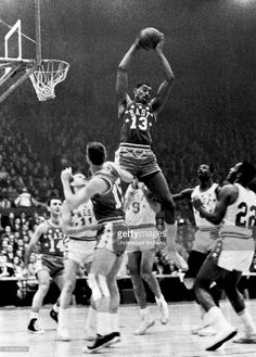 Wilt Chamberlain, Philadelphia (13), goes up high to snag a rebound in the NBA All-Star game, St Louis, Missouri, January 16, 1962. Below him are (l-r) Bob Cousey, Boston (14); Jerry West, Los Angeles (11); Tom Heinsohn, Boston (15); Bob Pettit, St Louis (9); Walt Bellamy, Chicago (8) and Elgin Baylor, Los Angeles (22).