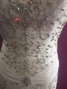 11.  WHITE Crown Collection gown detail of rhinestones and beading, showing waist detail.