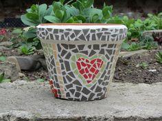 Mozaikový květináč ze srdce Květináč je z pálené hlíny, zdobený mozaikou z opracovaných úlomků dlaždic. Šířka květináče je 22cm, výška 17,5cm, váha 2 100g.