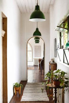 A line of pendant lights create depth and acts as a guide, pulling you into the main area of the house. A few pot plants give the home a lived-in feel
