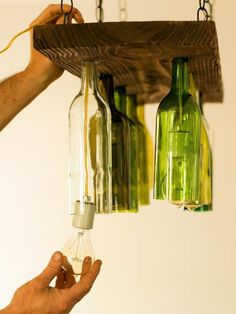 How To Make a Chandelier From Old Wine Bottles: Suspend bottle-holding plank from ceiling canopy with chain. Use caulk gun to add silicone along surface of drilled holes. Next, insert wine bottles up into holes until securely and snugly in place, then insert sockets up through the wine bottles and through drilled holes of plank. From DIYnetwork.com: