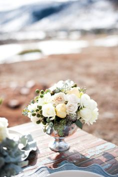 centerpiece idea - metal container, random feminine flowers and lovely interesting bits