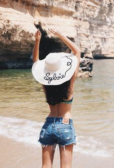 A roundup of the best blogger beach style for summer fashion inspiration | @sylviahaghjoo's embroidered name hat with cutoff denim shorts and bikini