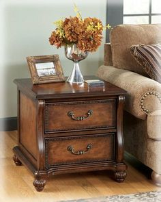"Traditional Dark Brown Shelton End Table by Famous Brand Furniture. $357.48. Veneer inlay border. Made with select cherry veneers. 24"" W x 24.5"" D x 23.75"" H. Style: Traditional Classics. Finish: Dark Brown. The flowing traditional design of the ""Shelton"" accent table collection features a rich finish and beautiful details to create a warm and inviting addition to any living room decor. The select cherry veneers are bathed in a dark brown finish that flows smoothly over the scro..."