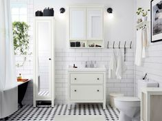 White bathroom with tiles, commode and tall cabinet with mirror door. Here with white sink and wall cabinet with mirrored doors.
