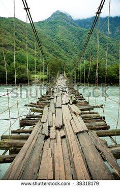 The hanging bridge over mountain river photo - stock photo