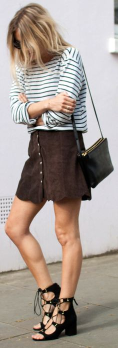 Lucy Williams is wearing a navy and white vintage striped tee with a dark brown suede button downed skirt from Reformation