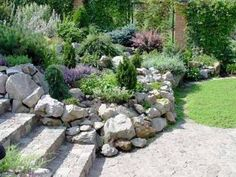 Beautiful rock garden design with natural stone wall, adds nice enclosure to the stairs an enables Raised Flowers (Christopher Alexander pattern) rock garden landscaping Sloped Backyard Landscaping, Landscaping With Rocks, Landscaping Ideas, Backyard Ideas, Modern Backyard, Landscaping Software, Rustic Landscaping, Landscaping Edging, Large Backyard
