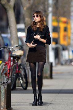 Alexa Chung | Moletom preto com saia de veludo vinho, meia calça e bota.
