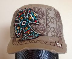 This distressed beige cadet cap features a dark brown screen printed Aztec pattern across the front of the hat, along with dark brown embroidery that follows the pattern. The hat also features a black fabric cross in a multicolored embroidered Aztec pattern and embellished with silver rhinestones; the front and bill of the cap.are distressed/torn for a fun 'worn' look.