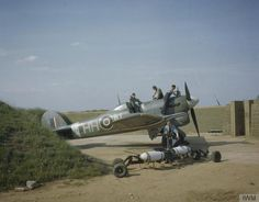 """Here is Hawker Typhoon Mark IB HH-N aka """"Dirty Dora"""" of No 175 squadron undergoing servicing at Colerne in a blast-walled dispersal point. The crew also has two dummy bombs for practice loading on to the wing racks. May Source: IWM (TR Ww2 Aircraft, Military Aircraft, World's Largest Snake, Hawker Tempest, Hawker Typhoon, Hawker Hurricane, Ww2 Planes, Royal Air Force, Wwii"""