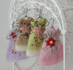 """Four tiny hand knit and embroidered Christmas dresses for tiny 4"""" Amelia Thimble dolls by Cindy Rice Designs."""
