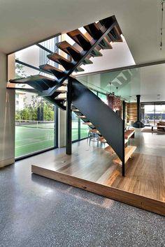 escalier demi-tournant en bois avec un garde-corps en métal noir