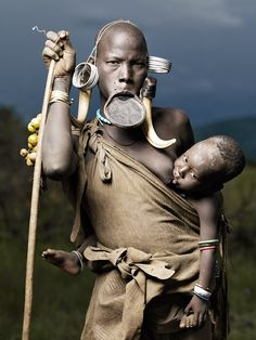 Portrait of Nadogomi and Bardomoye, Mursi tribe, Lower Omo Valley, Ethiopia    The clay disk inserted into a woman's lower lip is a Mursi tradition. The piercing begins around puberty, and it is stretched larger and larger in small intervals. Nadogomi is a mother of 5 children. The boy in the picture's name is Bardomoye. Around The Worlds, People Around The World, Joey Lawrence, Art Tribal, Tribu Mursi, Mursi Tribe, Baby Wearing, African Tribes, Tribal People
