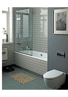 Smoke Grey glass subway tiles add a spa-like feel to this tub/shower combo bath.: