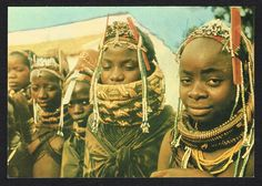 Muila young women with bride in Huila , ANGOLA , Portuguese AFRICA 1970. These young women are all close friends . The bride wears the traditional wicker-and-clay necklace that extends high up almost to her nose. Many weeks before the wedding they all spend many hours preening each other on a daily basis , and use their plastic combs as part of their headress : a pair of matching combs , one on each temple , or 1 comb centre forehead , always displayed vertically ( Angola 1970's ).