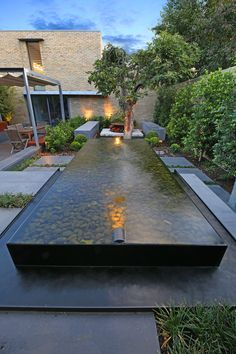 Infinity pool wet edge water feature with landscape lighting and rocks at the bottom Plunge Pool, Landscape Lighting, Water Features, Nook, Infinity, Custom Design, Sidewalk, Environment, Stainless Steel