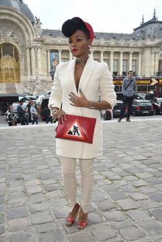 Janelle Monae wears a cream jacket and pants with a bold Geogina Men At Work Clutch and Nicholas Kirkwood heels.