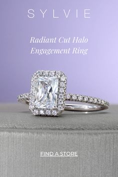 This gorgeous Radiant cut halo engagement ring includes a 1 carat, emerald-shaped diamond with a single halo of sparkling diamonds. The band features a train down both sides of shimmering, round-cut diamonds, making the total weight of this stunning setting come to 0.33 carats. SYLVIE Engagement Rings. Radiant Engagement Rings with Halo. 1 Carat Engagement Rings, Radiant Engagement Rings, Double Halo Engagement Ring, Classic Engagement Rings, Engagement Ring Styles, Designer Engagement Rings, Thing 1, Radiant Cut, Round Cut Diamond