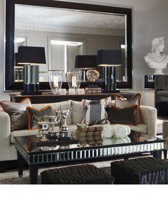 Espejo, mesa detras de sillon en sala