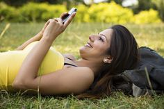 Woman using a mobile phone while resting on grass, New Delhi, India Delhi India, New Delhi, 20 Years, Grass, Things To Come, Stock Photos, Woman, Phone, Image
