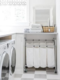 Clad in white and gray checkered floor tiles, this beautifully equipped laundry room features a 4 bin laundry sorter positioned beneath a gray quartz countertop topped with a white baroque mirror placed beside a window dressed in a gray and white trellis roman shade.