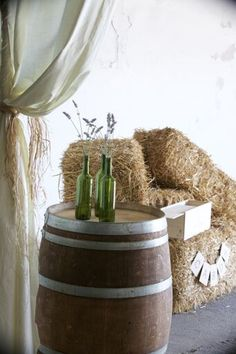 We love this looked created using our French Oak Wine barrels and Wine bottles filled with sprigs of lavender. The hay bales and soft draping perfectly finishes this rustic look.